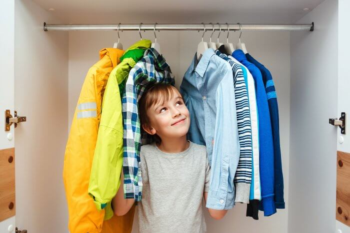 Preteen Boy Chooses Clothes In The Wardrobe Closet At Home. Kid